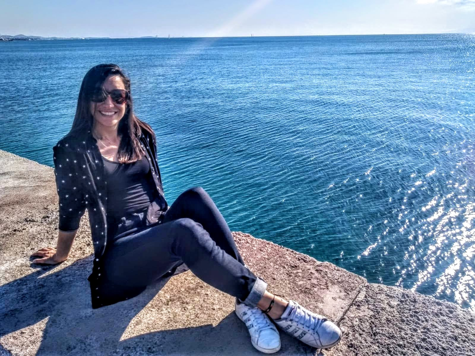 Carolina sitting by the sea at Flisvos Marina in Athens.  This is not a bikini photo, but a representation of a life change.  Her smile and relaxed position represents the happiness of being able to dedicate her life to help people on living healthier lives.