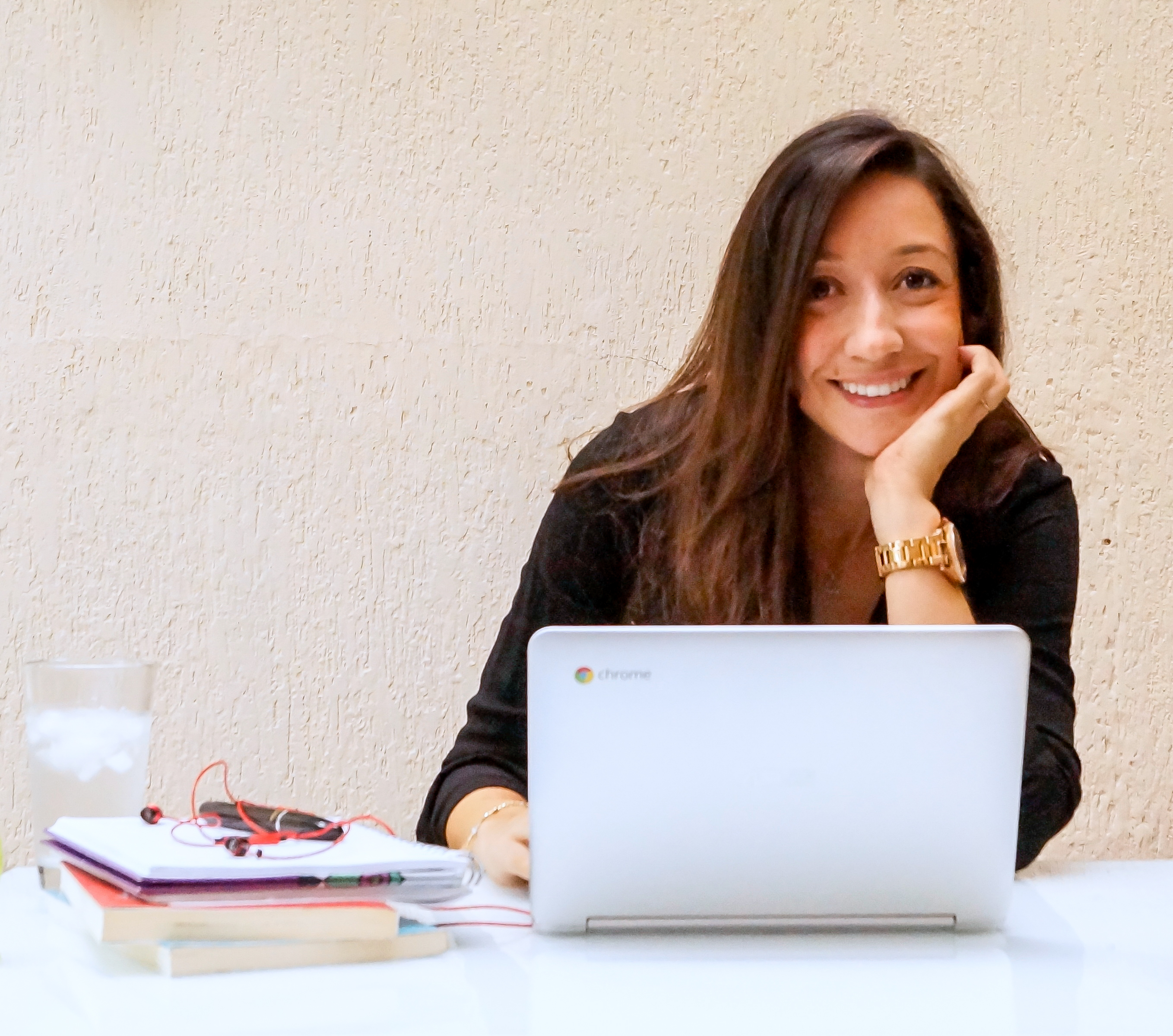 Carolina in front of her laptop, smiling.   This photo is a representation of her willingness to help people.  Health coach, nutrition advice & guidance towards a healthier lifestyle.